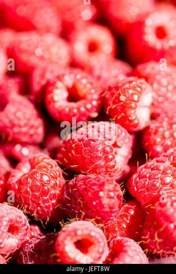 Full frame raspberries macro pink red detailed background. Vertical crop - Stock Image