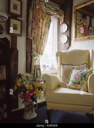 Floral Curtains And Matching Cushion On Cream Armchair In Cottage Living Room