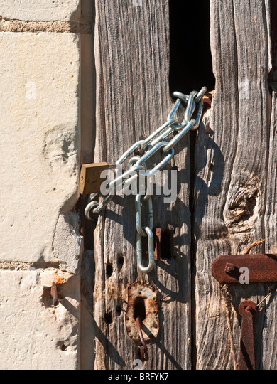 New Lock And Chain Fastening Old Barn Door   France.   Stock Image