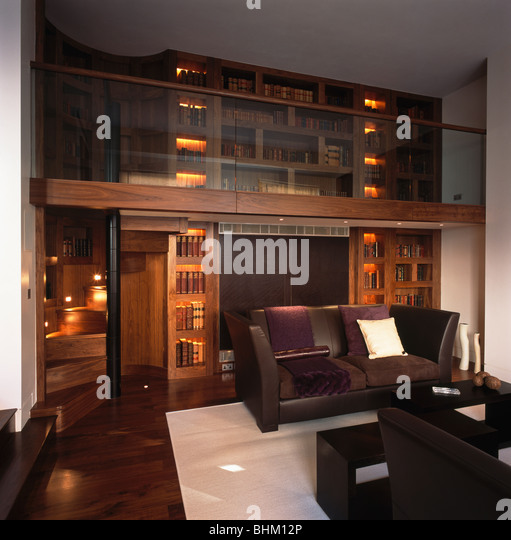 Brown Leather Sofas In Modern Double Height Library Living Room With Wall Lighting And White