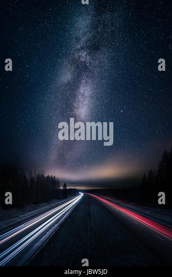 Scenic night landscape with milky way and highway - Stock Image