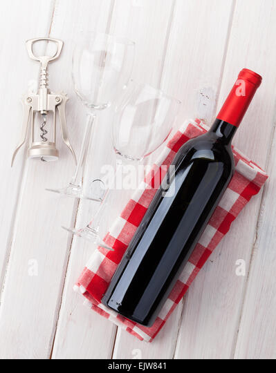 Red Wine Bottle, Glasses And Corkscrew On White Wooden Table Background    Stock Image