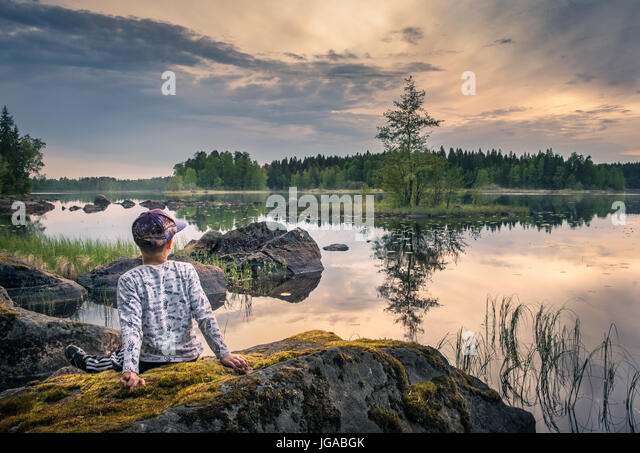 Boy sitting on the stone at scenic summer lake landscape in National Park, Finland - Stock Image