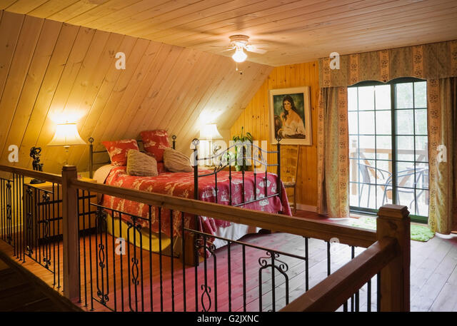 Master bedroom queen size bed on mezzanine inside a cottage style log home  Quebec Canada This