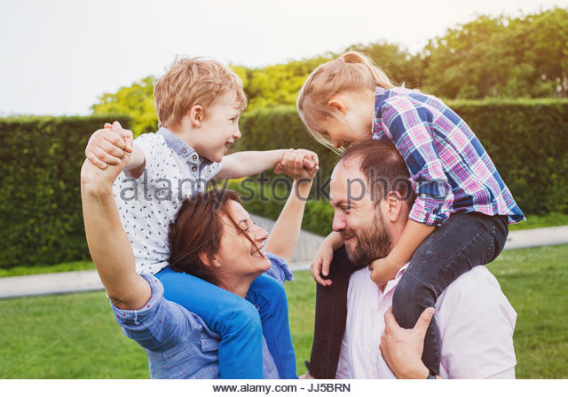 happy family with two kids outside in the green  park in summer - Stock Image