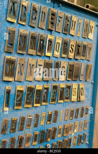metal letter stencils hanging on blue wall rack in factory stock image