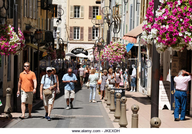 A busy street scene on a Saturday morning in Antibes, France.residents and tourists are out and about enjoying the - Stock Image