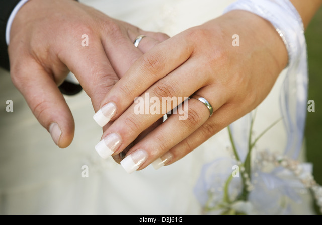 bride and grooms hands showing wedding rings stock image