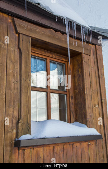 Window With Icicles Hanging Down Snow On The Sill And Capped Mountains