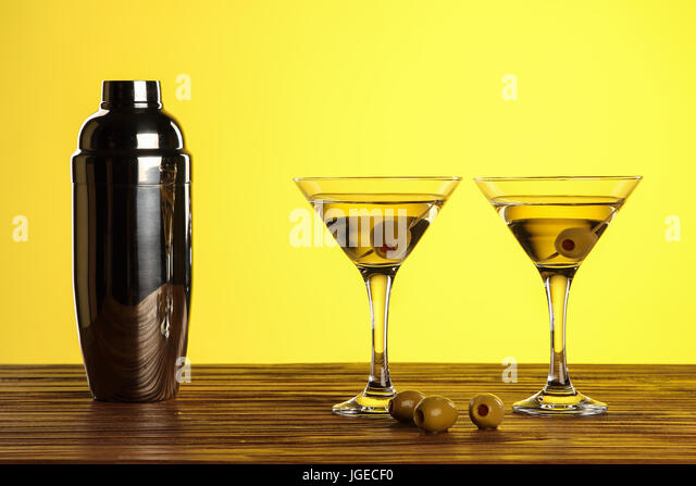Two cocktails in martini glasses with green olives and shaker on a wooden surface against yellow background with - Stock Image