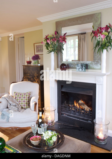 white armchair beside fireplace with lit fire in country living room with drinks tray on ottoman
