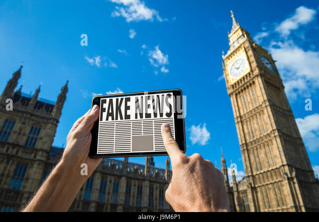 Reader scrolling through fake news stories on his tablet computer in front of the Houses of Parliament at Westminster - Stock Image