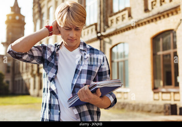 Handsome confused guy troubled with assignment - Stock Image