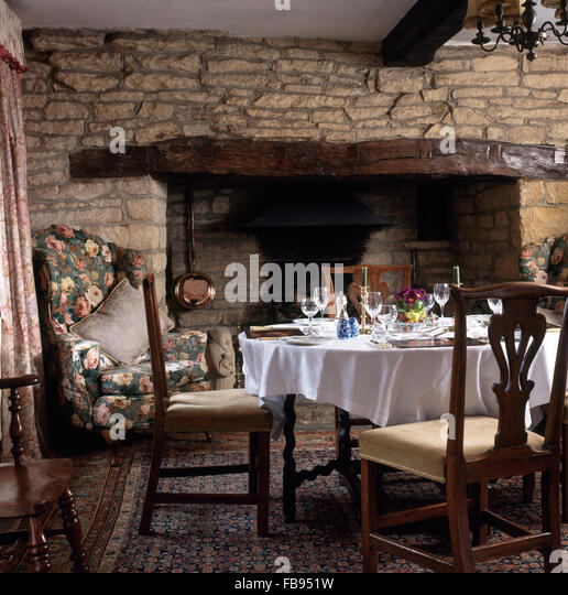 Vintage Chairs At Table With A White Cloth Set For Lunch In Front Of Inglenook Fireplace