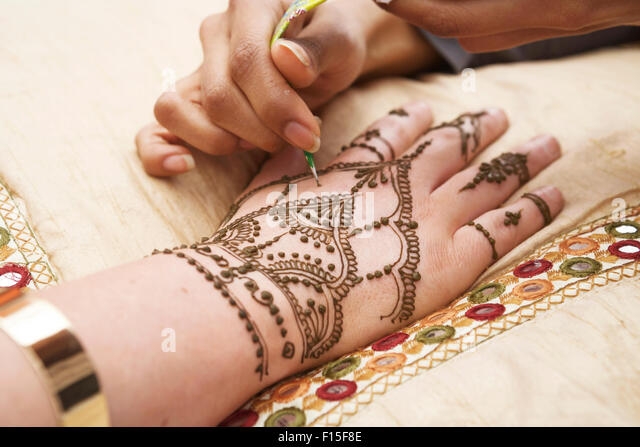 Henna patterns, hand being decorated / tattooed with hena. Henna painting. Henna  hand