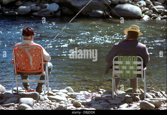 Two Retired Fishermen Relax On Their Lawn Chair On The Banks Of Rocky  Mountain Stream In
