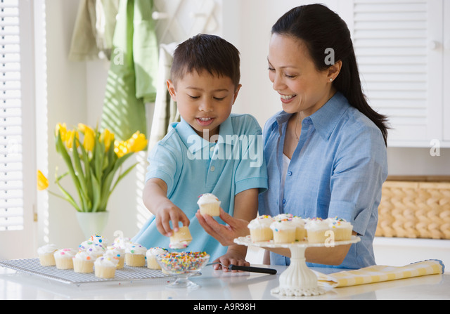 asian mother and son decorating cupcakes stock image