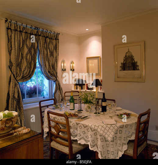 Lace Tablecloth On Table Set For Dinner In Cream Dining Room With Patterned Curtains At Window
