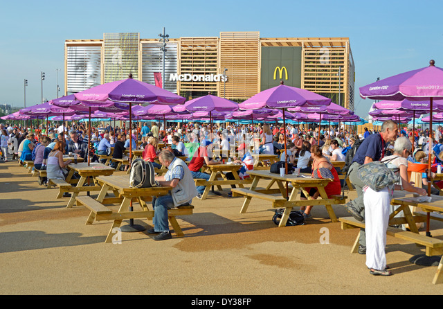 Picnic Benches And Parasols In The London 2012 Olympic Park With Temporary McDonalds Restaurant Beyond