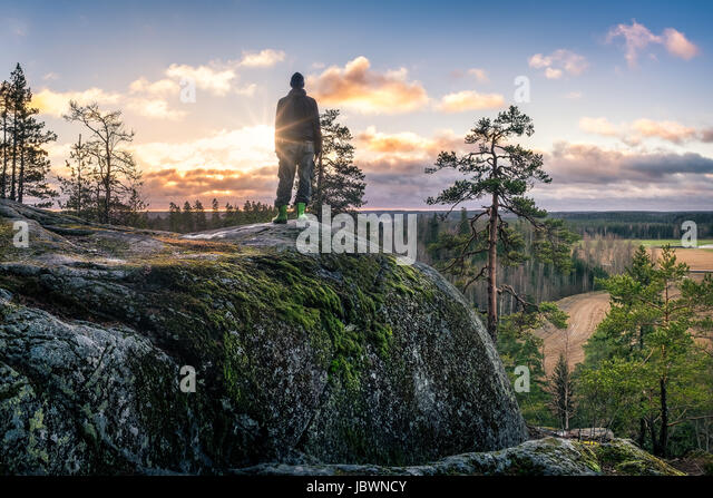 Hiker standing front of beautiful landscape at early morning - Stock Image