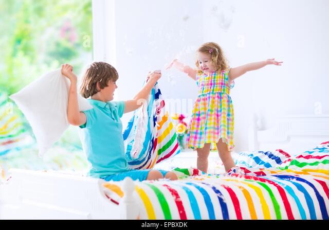 Two Children Happy Laughing Boy And Cute Curly Little Girl Having Fun At Pillow Fight