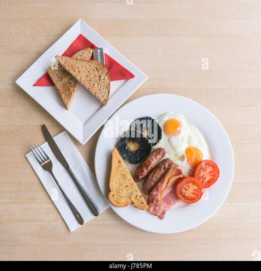 An overhead view of a full English breakfast; Food; Morning meal; Fry up; Calories; Toast; Eggs; Bacon; Sausages; - Stock Image