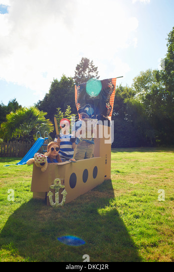 Two Brothers And Sister Playing In Garden With Homemade Pirate Ship   Stock  Image