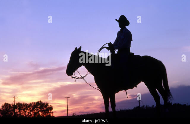 Silhouette of a American cowboy on his horse with sunset in the background - Stock Image