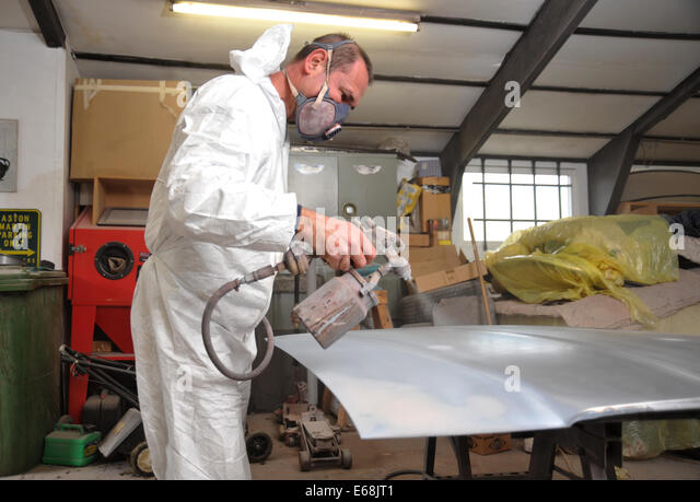 car repair and restoration spray gun applying paint to car wing. Black Bedroom Furniture Sets. Home Design Ideas