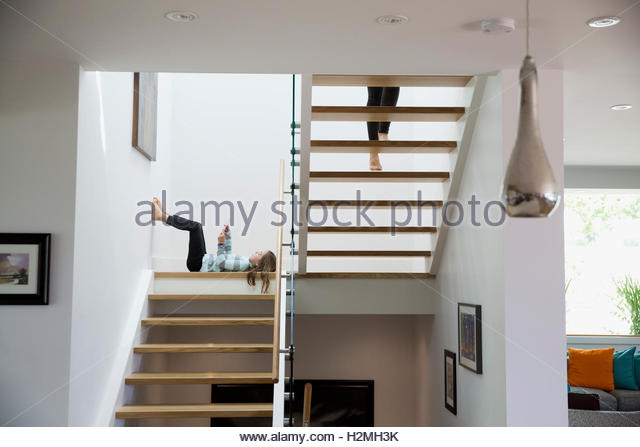 Girl Using Digital Tablet Laying On Wooden Stairway Landing   Stock Image