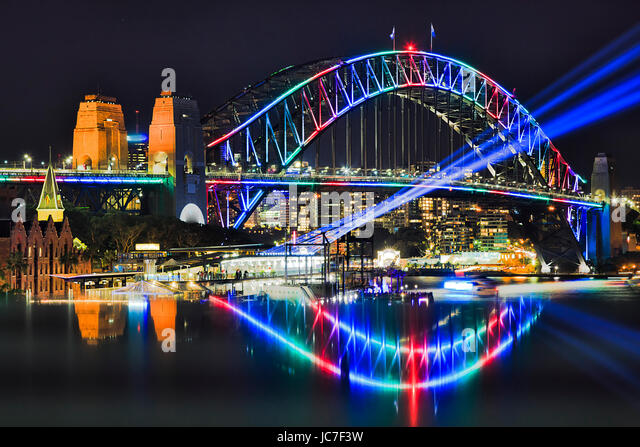 Multi colour arch of Sydney Harbour bridge with blurred reflection during Vivid Sydney festival in 2017. Blue light - Stock Image