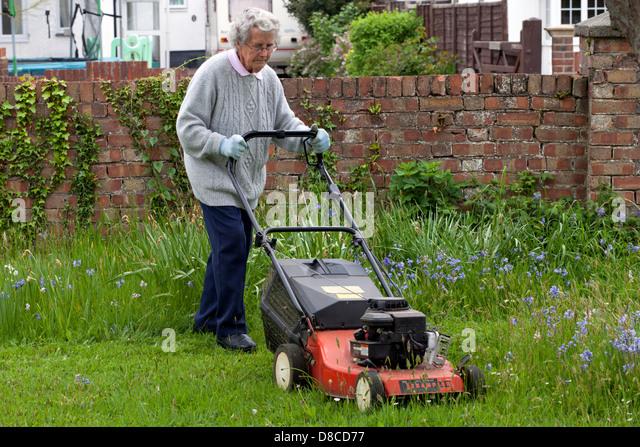 Cutting grass uk stock photos cutting grass uk stock for Lawn mower cutting grass