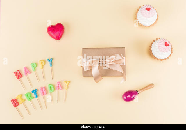 Top view of happy birthday lettering, envelope with ribbon and delicious cupcakes on pink, birthday party concept - Stock Image