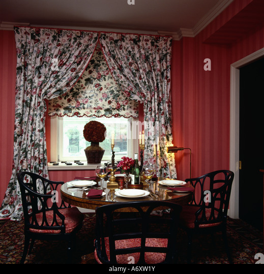 Table In Red Diningroom With Patterned Floral Drapes And Blind