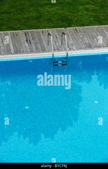 aerial view of an outdoor swimming pool with wood deck and lawn stock image