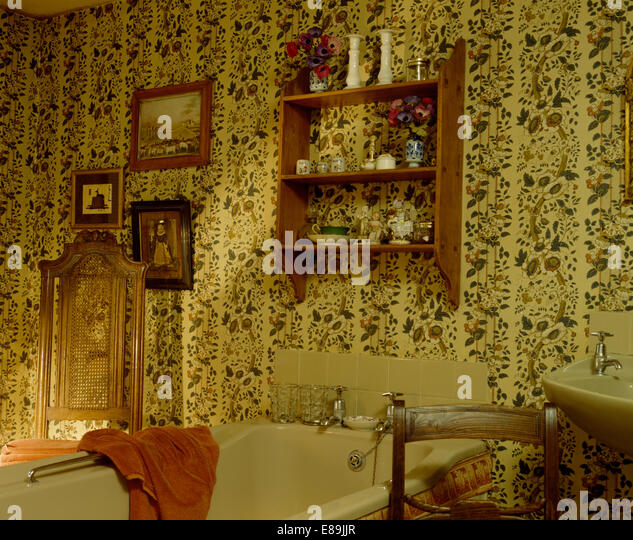 Small Pine Shelf Unit Above Beige Bath In Country Bathroom With Floral Wallpaper Stock Image