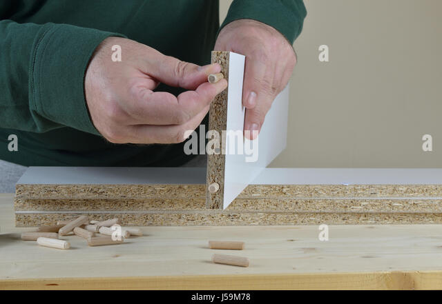 Man inserting wooden dowels into a particle board of a new piece of furniture - Stock Image