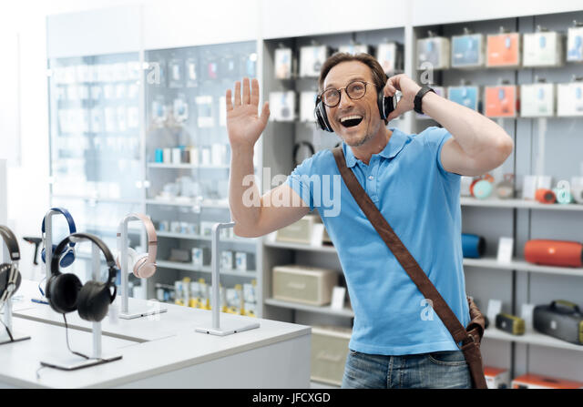 The song of my childhood. Waist up shot of an extremely excited man testing out the latest model of headphones while - Stock Image
