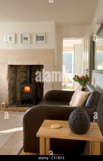 leather sofa by a cosy log burning stove in a living room corner stock