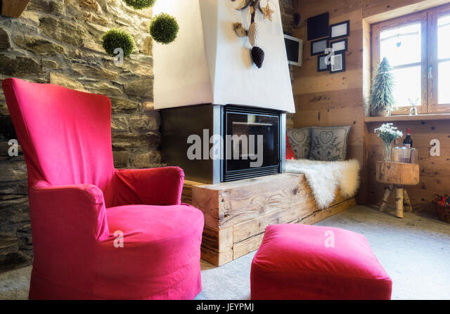 Cozy interior of a rustic chalet with modern fireplace - Stock Image