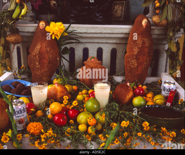altar prepared with flowers food and pan de muerto bread of the dead