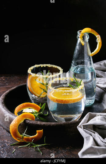 Tonic water cocktail with rosemary and orange. Two glasses and bottle with zest sugar and bubbles in terracotta - Stock Image