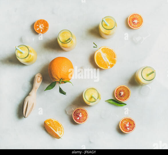 Healthy yellow smoothie with citrus fruit, ginger and ice - Stock Image