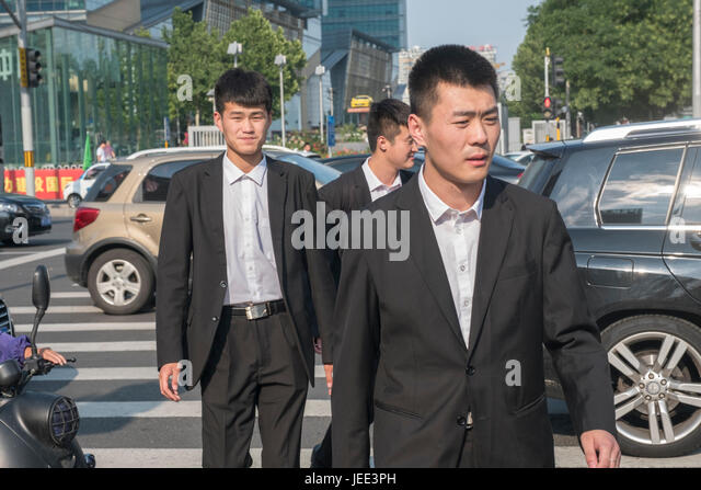 Chinese men wear suits on the street in Beijing, China. - Stock Image