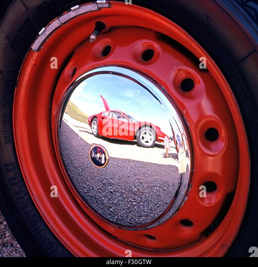 a red ferrari reflected in the hubcap of another vehicle gaydon england