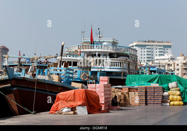 Cargo In Front Of An Old Wooden Ship Dhow Or Dau On Dubai Creek