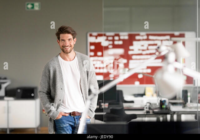 Dynamic businessman standing in office, smiling - Stock Image