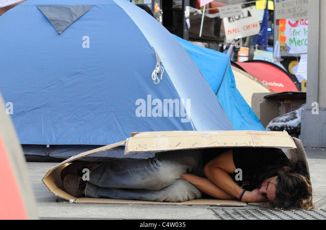 A man sleeps in a cardboard box during the Indignantsu0027s occupation of Puerta del Sol & Protester Sleeping In Tent City Stock Photos u0026 Protester Sleeping ...