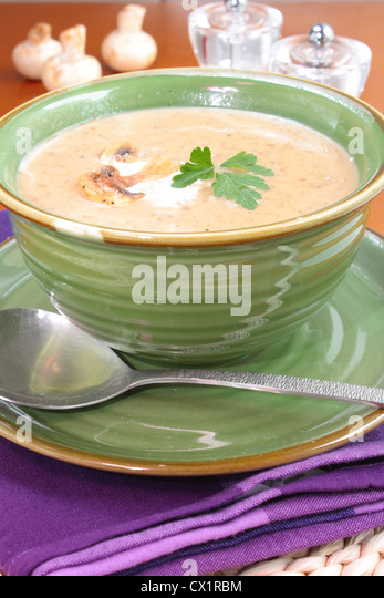 A Bowl Of Homemade Cream Of Mushroom Soup Served In A Large Green Bowl