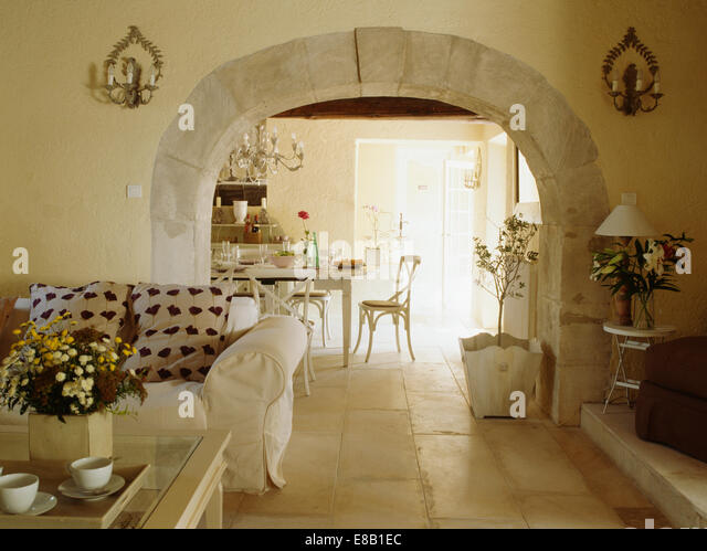 Stone Flooring In French Country Living Room With White Sofa Beside Stone Edged  Arch To